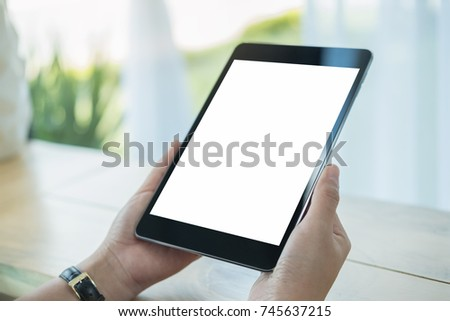 Mockup image of hands holding black tablet pc with blank white screen on wooden table in cafe #745637215
