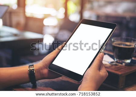 Mockup image of hands holding black tablet pc with blank white screen with white coffee cup and tea on wooden table in cafe #718153852