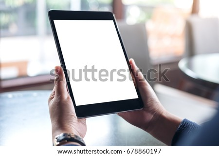 Mockup image of hands holding black tablet pc with white blank screen in modern cafe - Shutterstock ID 678860197