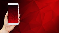 Mockup image of hands holding white mobile phone with red screen on polygonal background