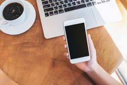Mockup image of hands holding white smartphone with blank black screen ,laptop and coffee cup on wooden table in cafe