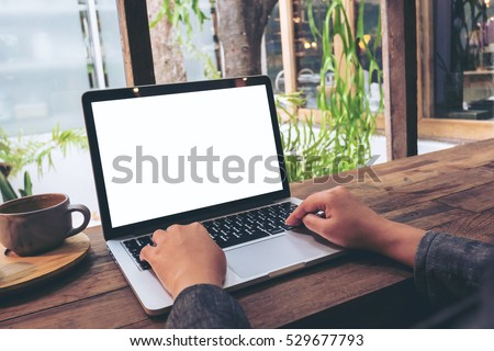 Mockup image of hands using laptop with blank white screen on vintage wooden table in cafe #529677793