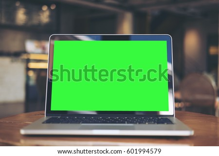 Mockup image of laptop with blank green screen on wooden table in vintage cafe