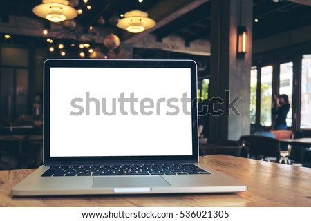 Mockup image of laptop with blank white screen on wooden table in dark modern cafe