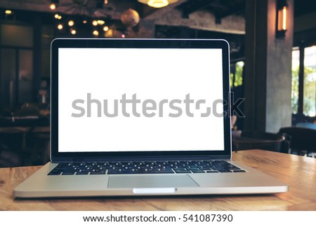 Mockup image of laptop with blank white screen on wooden table in dark modern cafe #541087390