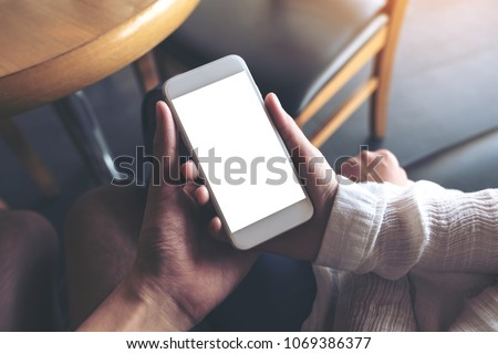 Mockup image of man and woman's hands holding and looking at white mobile phone with blank desktop screen together