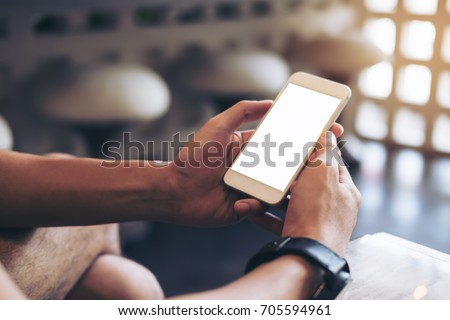 Mockup image of man's hands holding white mobile phone with blank screen in modern cafe #705594961