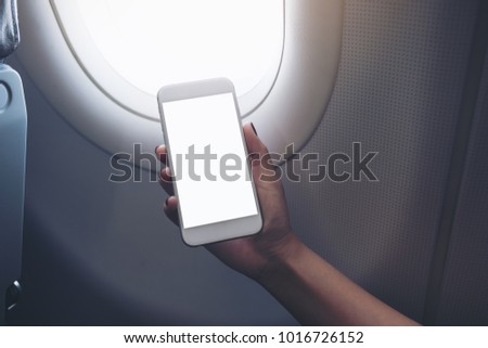Mockup image of woman's hand holding a white smart phone with blank desktop screen next to an airplane