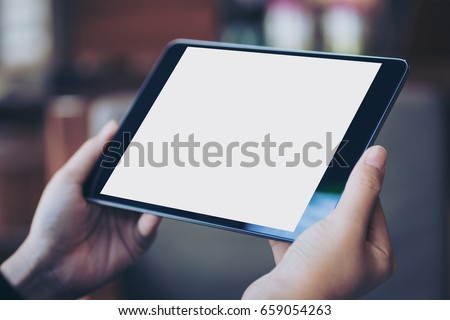 Mockup image of woman's hand holding black tablet pc with blank white screen in wooden cafe