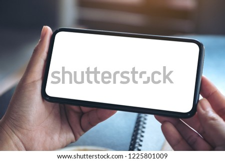 Mockup image of woman's hands holding and using a black mobile phone with blank screen horizontally for watching