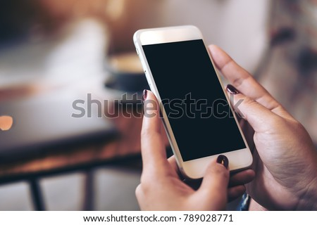 Mockup image of woman's hands holding mobile phone with blank black desktop screen in cafe