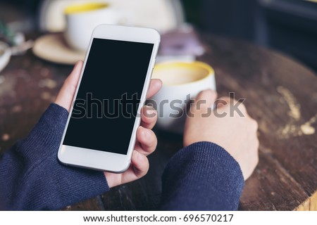 Mockup image of woman's hands holding white mobile phone with blank black screen and a coffee cup on wooden table in vintage cafe
