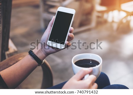 Mockup image of woman's hands holding white mobile phone with blank black screen while drinking coffee in modern loft cafe