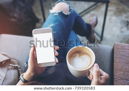 Mockup image of woman's hands holding white mobile phone with blank screen on thigh and coffee cup in cafe #739320583