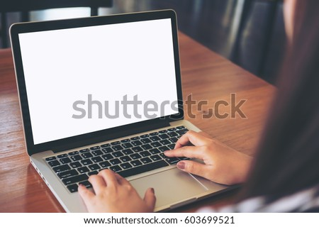 Mockup image of woman's hands using laptop with blank white screen on vintage wooden table in loft cafe #603699521