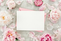 Mockup invitation, blank paper greeting card, pink envelope and peonies on gray stone table. Flower background. Flat lay, top view.