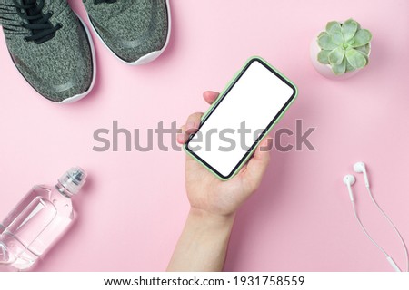 Mockup - man's hand holds a smartphone on a pink background with Sneakers, bottle of water, white headphones. Sport concept. Place fot text, Flat lay. Stock fotó ©