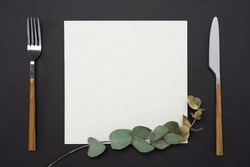 Mockup menu, recipe or cookbook. knife, fork, square paper mockup decorated with gold eucalyptus branch on a black table.