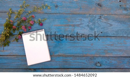 Mockup - notebook on wooden background. A sketchbook and a bouquet of clover lie on old blue boards. Flatlay for backgrounds, texts, desktops, banners, covers, postcards, to-do lists.