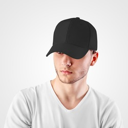 Mockup of a black baseball cap on a guy's head, looking from under a visor, front view, empty panama for design presentation. Sun protection headdress template. Fashionable sports hat for hip hop, rap