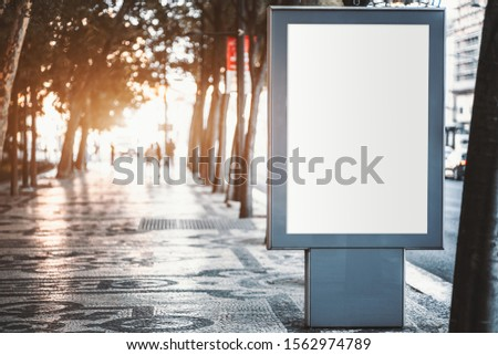 Mockup of a blank information poster on paving-stone outdoors; an empty vertical street banner template in a park; an outdoor billboard placeholder mock-up on a city boulevard in an alleyway