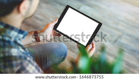 Mockup of a man holds tablet computer with isolated screen in his hands. View from above. Clipping path.