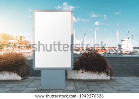 Mockup of a vertical blank ad poster in urban settings near commercial docks; an empty street banner template on the pier; an outdoor billboard placeholder mock-up in a port area with boats and ships ストックフォト ©