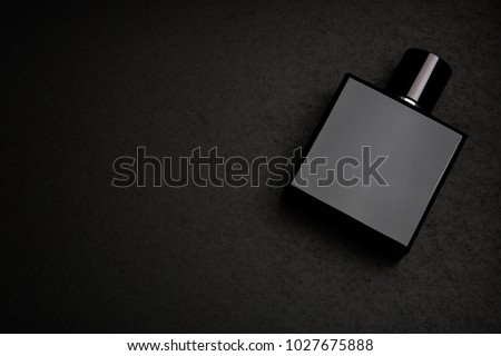 Mockup of black fragrance perfume bottle mockup on dark empty background. Top view. Horizontal