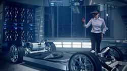 Mockup of Electric Vehicle: Automotive Female Professional Engineer working on design of Electric Car using Futuristic Augmented Reality Headset. High-tech facility. Electric car chassis.