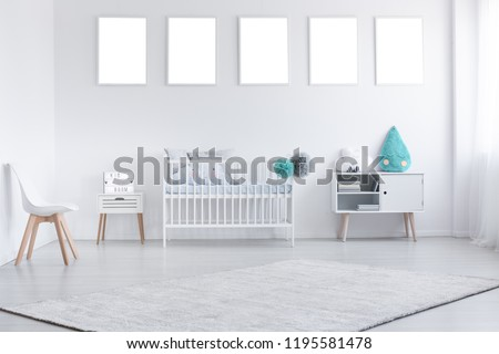 Mockup of empty posters above cradle in white baby's room interior with chair and carpet. Real photo