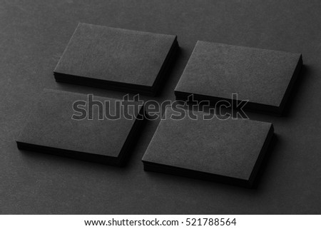 Mockup of four black business cards stacks arranged in rows at black paper background.
