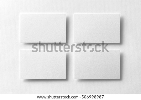 Mockup of four white business cards arranged in rows at white design paper background.