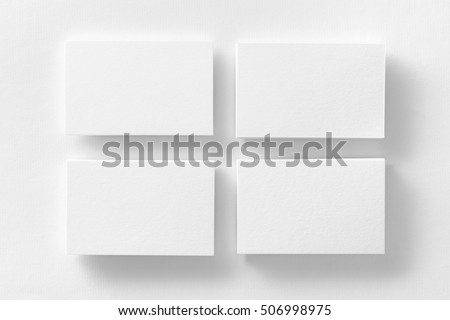 Mockup of four white business cards stacks arranged in rows at white design paper background.