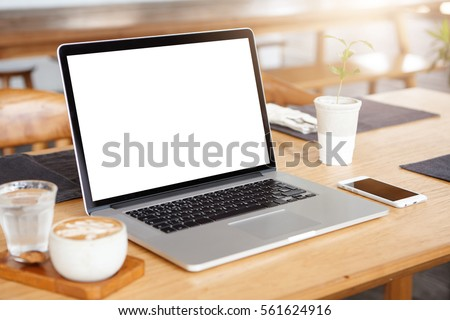 Mockup of generic laptop computer with blank copy space screen for your text or advertising content. Workspace of young freelancer: open notebook pc, cell phone and cappuccino on wooden table