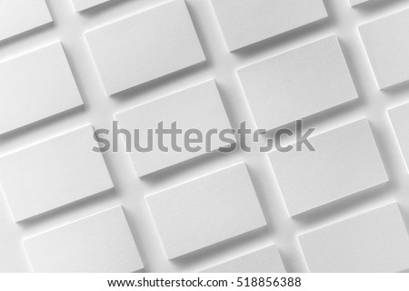 Mockup of horizontal business cards stacks arranged in rows at white textured paper background. #518856388