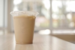 mockup of iced coffee milk in a plastic cup inside a cafe