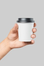 Mockup of men's hand holding white paper cup with black cover isolated on grey background