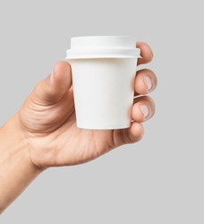 Mockup of men's hand holding white paper cup with white cover isolated on grey background