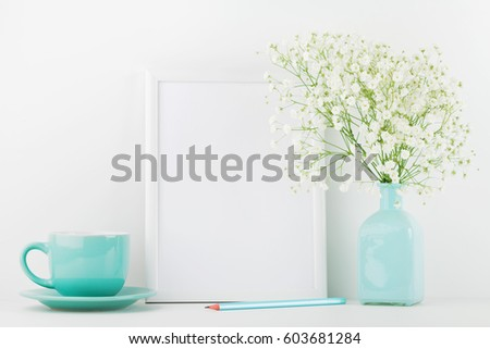 Mockup of picture frame decorated flowers in vase and coffee cup on white table with clean space for text and design your blogging.  #603681284