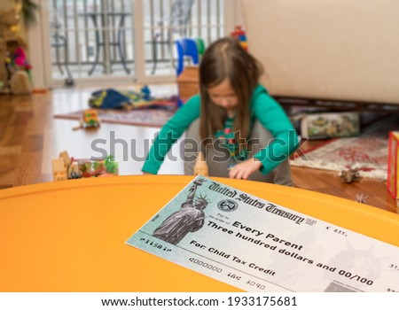 Mockup of US Treasury illustrative check for child tax credit for a small girl to illustrate American Rescue Plan Act of 2021 payments Stock photo ©