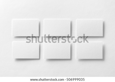 Mockup of white business cards arranged in rows at white design paper background.