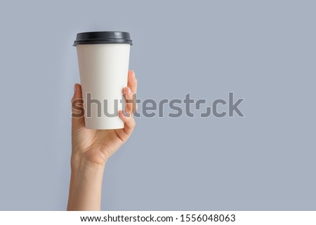 Mockup of woman hand holding up a Coffee paper cup isolated on grey background. Front view