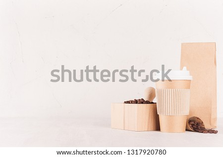 Mockup packing for coffee products and shop - brown paper cup, packet and mortar with coffee beans on white wood table, copy space, copy space. #1317920780