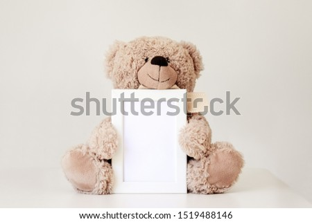 Mockup. Soft beige teddy bear toy holding white clean mock up frame with copy space sitting at light grey background. Empty space. Baby children concept.  Foto stock ©