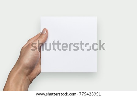 Mockup square empty blank white postcard holds the man in his hand. Isolated on a gray background #775423951