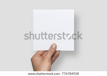 Mockup square empty blank white postcard holds the man in his hand. Isolated on a gray background #776784928