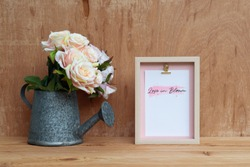 Mockup Still life Picture frame and at watering can with Bouquet of roses on rusty wood. Valentines Day Background concept. Mock up with photo frame for your picture or text
