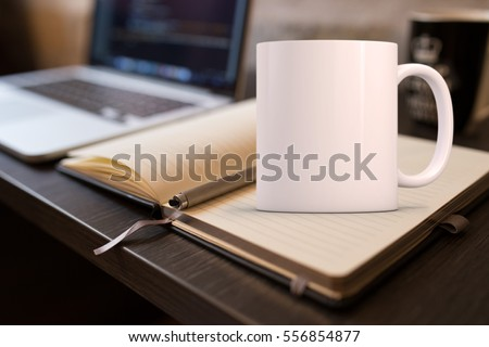 Mockup Styled Stock Product Image, white mug that you can add your custom design/quote to. Mug is on an open notebook next to a laptop. #556854877
