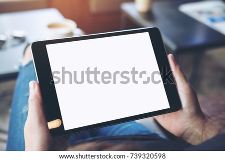 Mockup top view image of a woman sitting cross legged and holding black tablet pc with blank white screen on thigh in cafe - Shutterstock ID 739320598