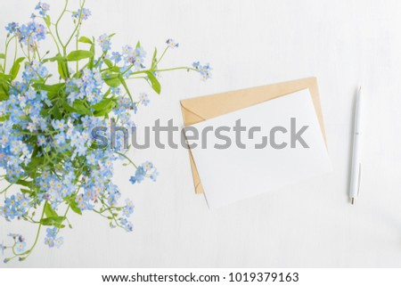 Mockup white greeting card and envelope with blue flowers and light background